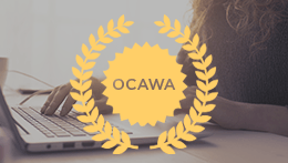 Person typing on laptop with OCAWA medallion