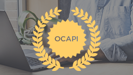Person typing on laptop with OCAPI medallion