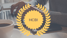 Person typing on laptop with HCBI medallion