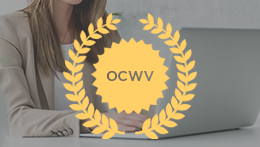 Person typing on laptop with OCWV medallion