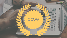 Person typing on laptop with OCWA medallion