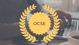 Person typing on laptop with OCSE medallion