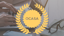 Person typing on laptop with OCASA medallion