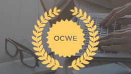 Person typing on laptop with OCWE medallion